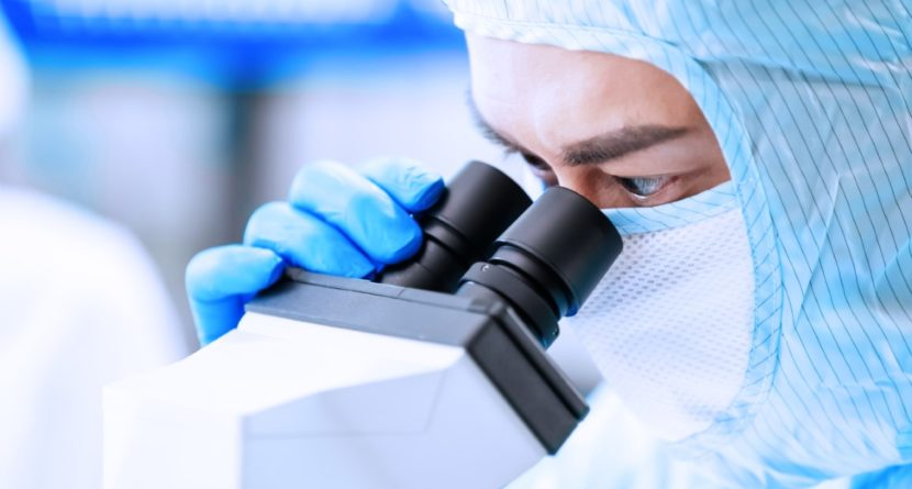 closeup of asian male scientist use microscope to do biotechnology research with cleanroom clothes and conduct experiments in the laboratory