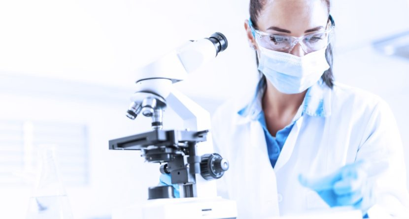 Female lab technician in protective glasses, gloves and face mask sits next to a microscope and conical flask, looking aside on the desk.