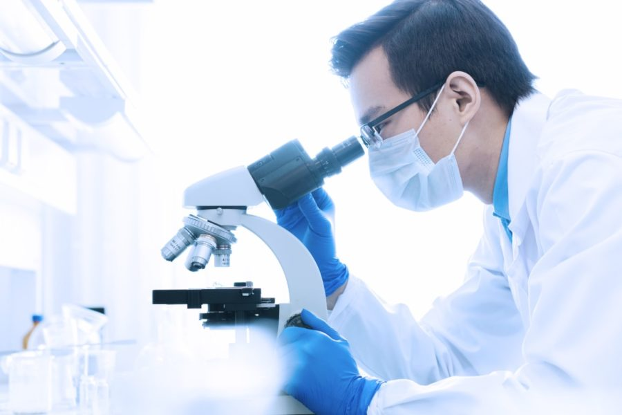 Young Chinese scientist or researcher in protective workwear studying new virus in microscope to develop antidote for fighting coronavirus